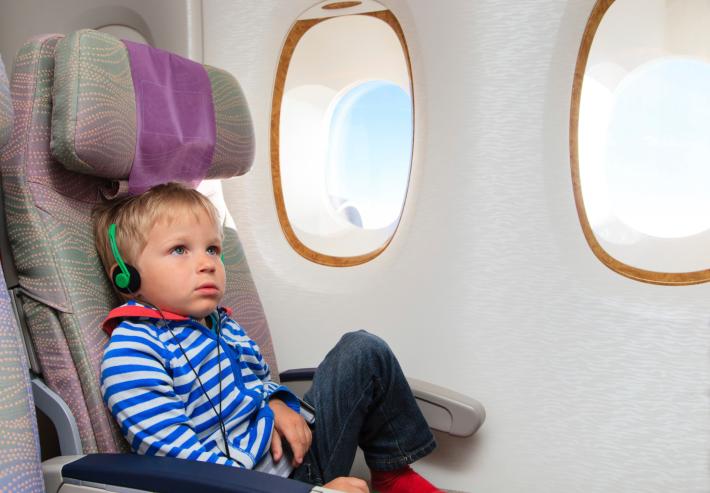 little boy watching tv in flight