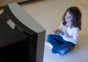 Young Girl with Remote Control Watching TV
