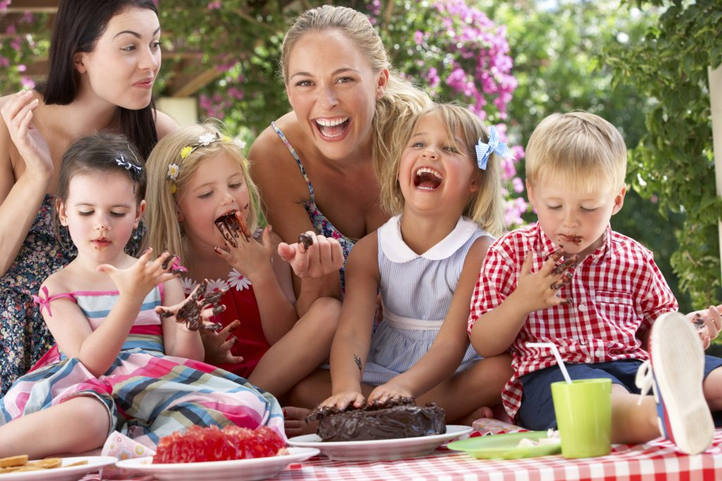 Children And Mothers Eating Cake At Outdoor Tea Party