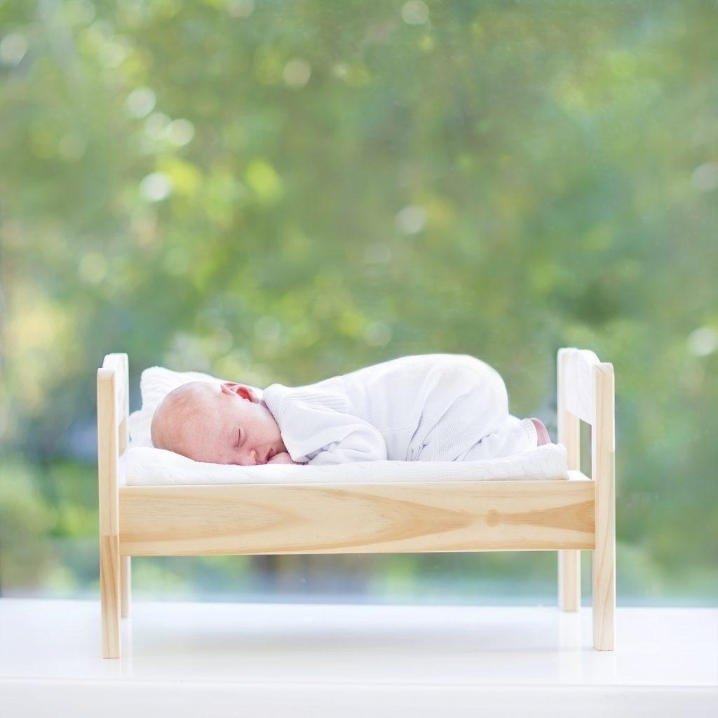 Newborn baby sleeping in toy bed next to big window