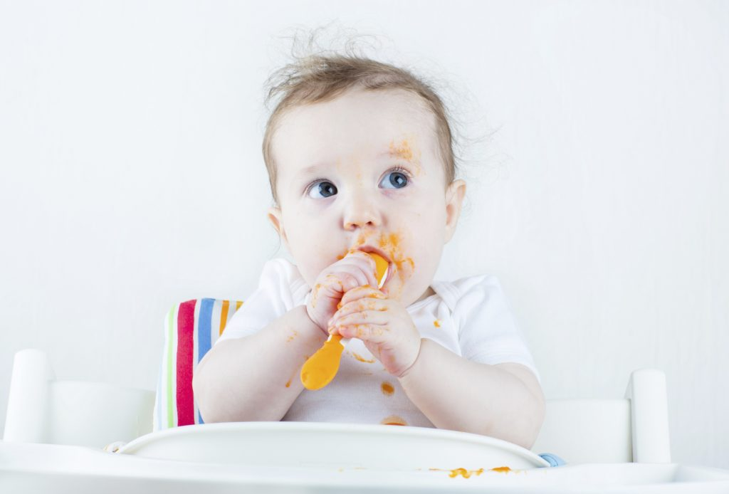 Sweet messy baby eating carrot in white high chair