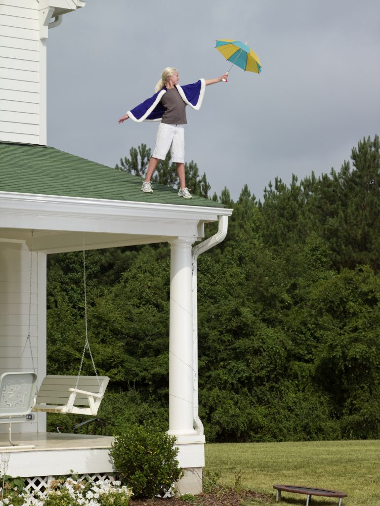 Girl (10-11) wearing cape and holding umbrella, preparing to jump off roof of house onto small trampoline