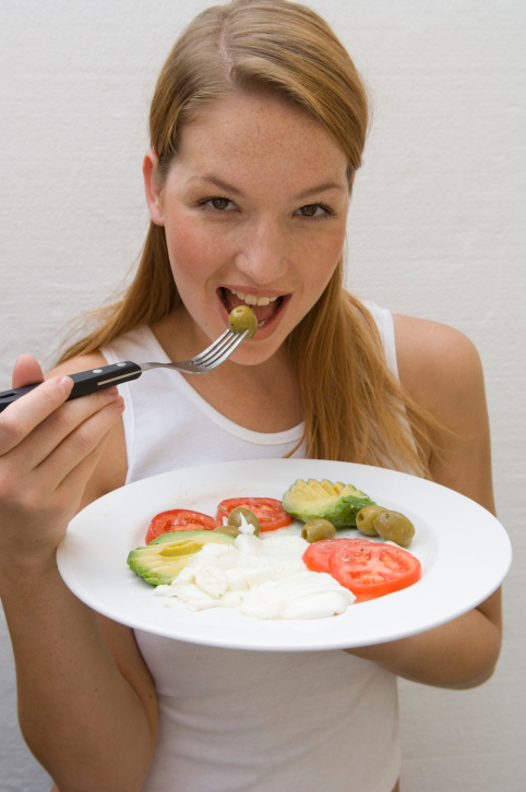 Portrait of a young woman eating an olive with a fork
