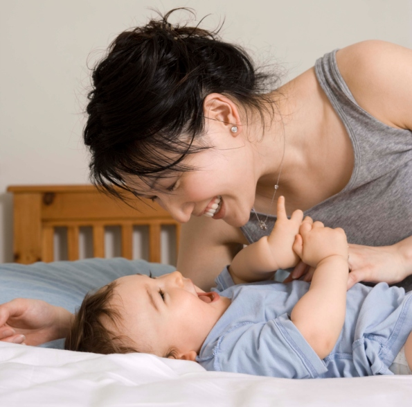 Mother playing with son on bed