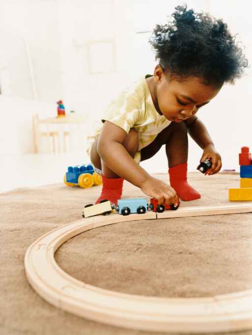 Young Girl Playing with a Toy Train