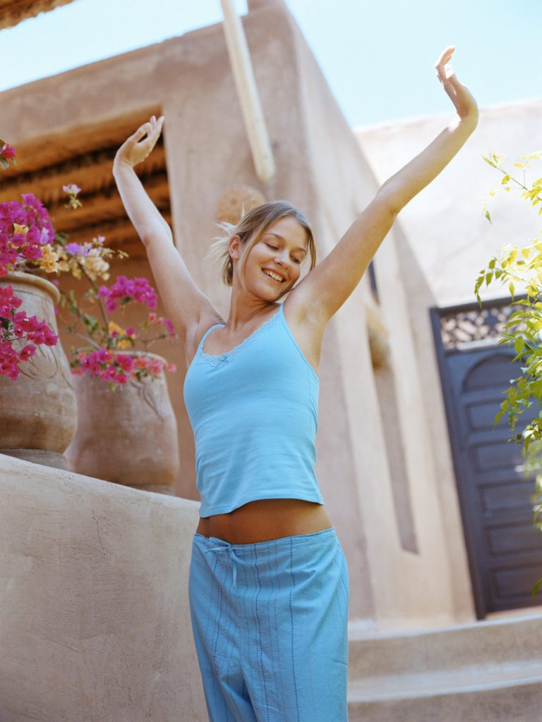 Young woman standing outdoors, arms raised, smiling