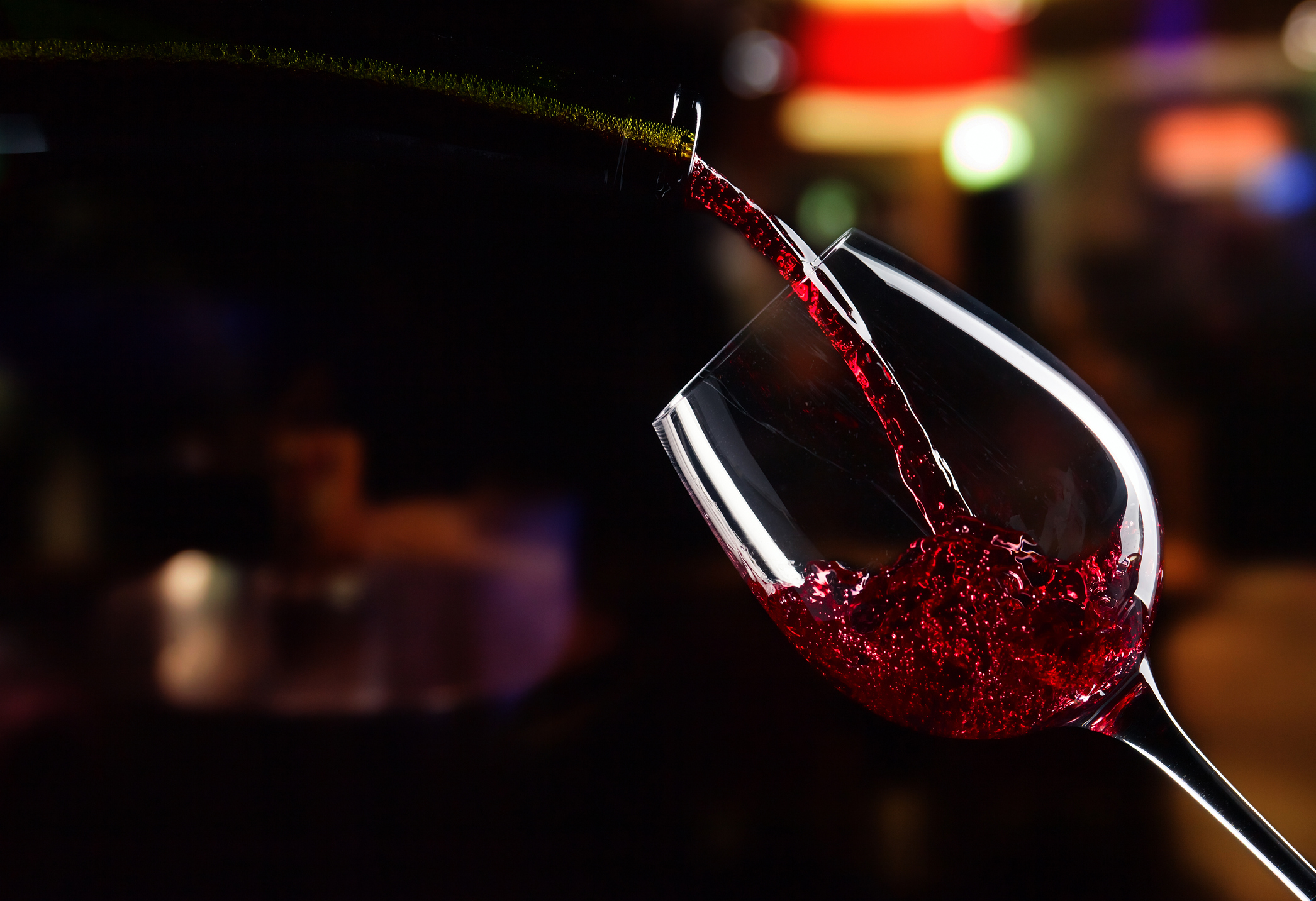 bottle and glass with red wine on dark background